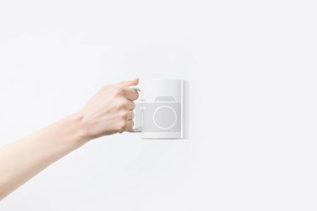 cropped shot of woman holding white mug in hand isolated on white
