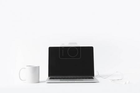 close up view of laptop with blank screen, earphones and white mug isolated on white