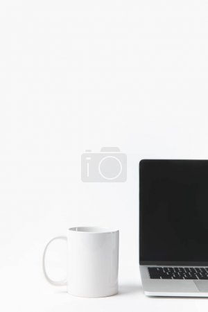 Photo for Close up view of laptop with blank screen and white mug isolated on white - Royalty Free Image