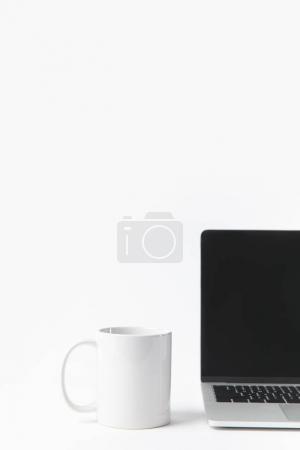 Photo pour Vue rapprochée de l'ordinateur portable avec écran blanc et tasse blanche isolé sur blanc - image libre de droit