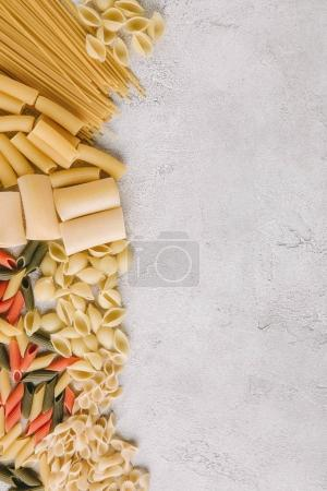 Photo for Top view of different raw pasta spilled on concrete surface - Royalty Free Image