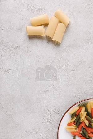 top view of two types of raw pasta on concrete tabletop