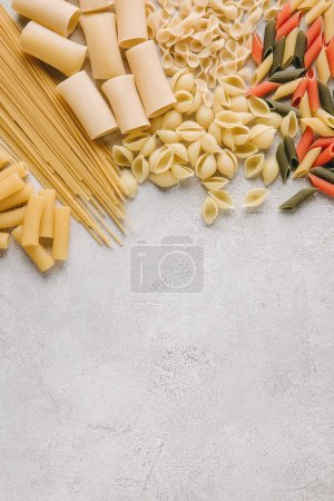 top view of various raw pasta spilled on concrete surface