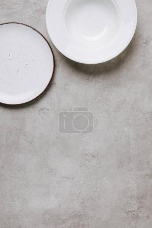 top view of empty plates on concrete tabletop