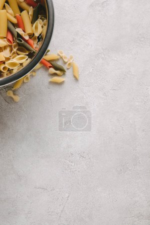 top view of raw pasta in bowl on concrete tabletop