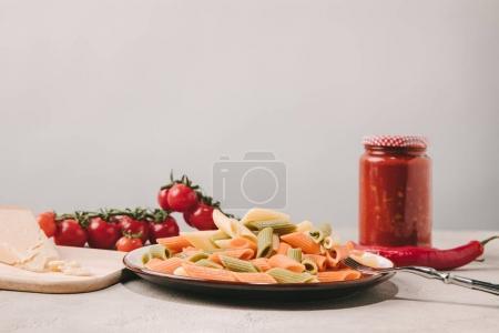 Photo pour Pâtes colorées sur plaque avec différents aliments sur fond sur la surface du béton - image libre de droit