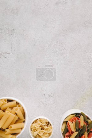top view of various types of raw pasta in bowls on concrete tabletop