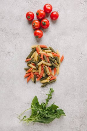 top view of raw colorful pasta with tomatoes and arugula on concrete surface