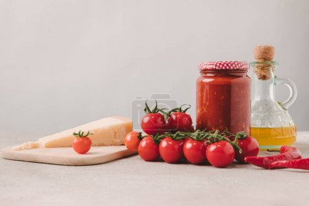 cherry tomatoes with cheese, ketchup and olive oil on concrete tabletop, ingredients of italian cuisine
