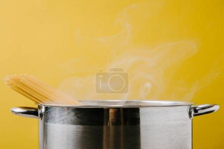 Photo for Delicious spaghetti boiling in stewpot isolated on yellow - Royalty Free Image