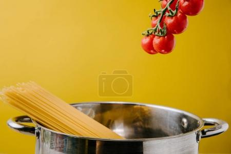 Photo for Spaghetti boiling in stewpot with branch of cherry tomatoes above isolated on yellow - Royalty Free Image