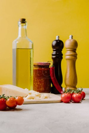 cherry tomatoes with cheese and spices for pasta on concrete tabletop, ingredients of italian cuisine