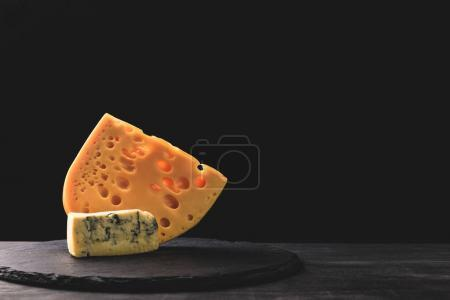 Close up view of emmental and blue cheese on board on black