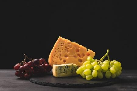 Photo for Blue cheese and emmental on board with grapes on black - Royalty Free Image