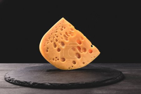 Close up shot of emmental cheese on board on black
