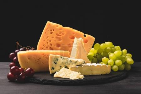 Closeup shot of different types of cheese on board with grapes on black