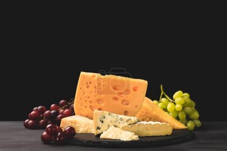 Photo pour Different types of cheese on board with grapes on black - image libre de droit