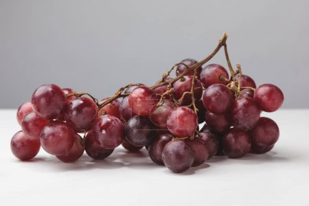 Close up view of pile of red grapes on gray