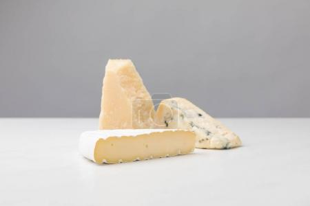 Close up view of brie, cheddar and blue cheese on gray