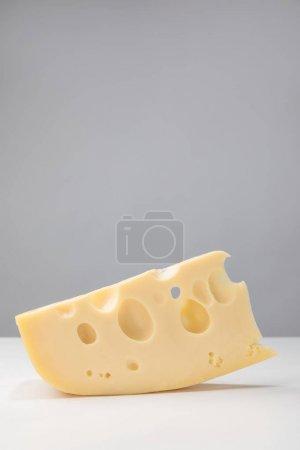 Close up image of maasdam cheese on gray