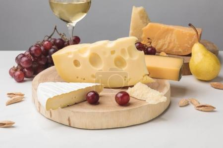 Photo for Different types of cheese on wooden boards, wine glass, fruits and almond on gray - Royalty Free Image