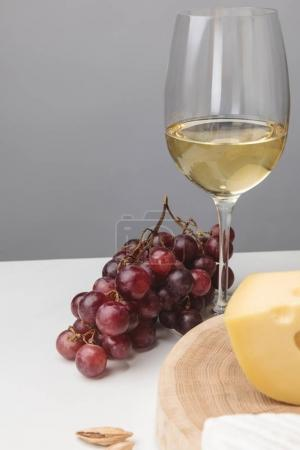 Photo for Partial view of maasdam cheese on wooden board, wine glass, almond and grapes on gray - Royalty Free Image