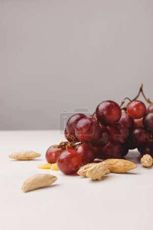 Close up view of grapes and almond on gray
