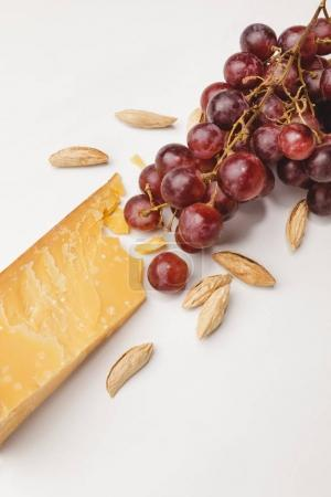 Closeup shot of parmesan cheese, almond and grapes on white