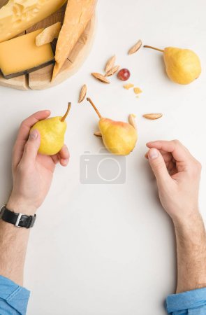 Cropped image of man with pear, almond and different types of cheese on wooden board on white