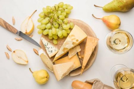 Photo pour Top view of different types of cheese on wooden board surrounded by knife, fruits, almond, baguette and wine glasses on white - image libre de droit