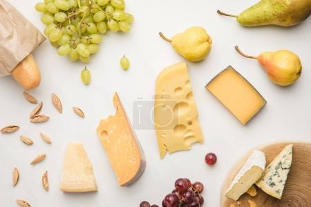 Photo for Top view of different types of cheese, grapes, pears, almond and baguette on white - Royalty Free Image