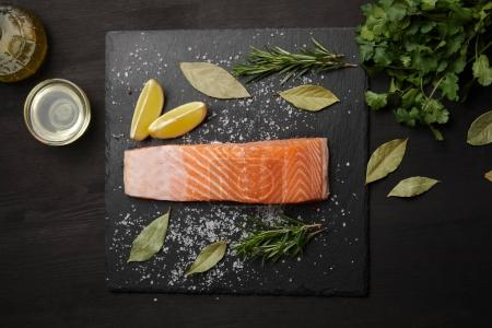 Piece of salmon with salt on black table with lemon and herbs