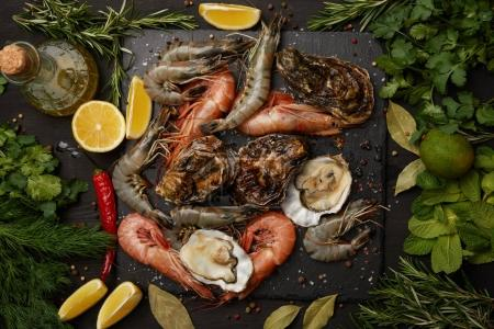 Photo for Shrimps and oysters on slate board with herbs and lemons - Royalty Free Image