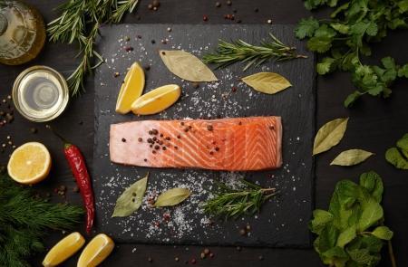 Photo pour Saumon rouge de poisson avec sel et poivre à bord par des herbes et des citrons - image libre de droit