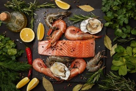 Photo for Raw salmon and assorted seafood with herbs and lemons on dark background - Royalty Free Image