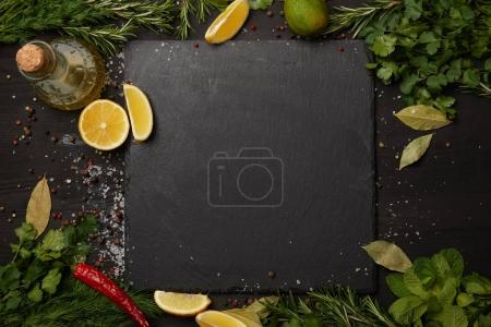 Photo for Black slate board with fresh herbs and lemon slices with olive oil - Royalty Free Image