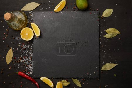 Dark slate board with spices and lemon slices