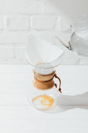 Photo for High angle view of pouring hot water from kettle into chemex with filter cone - Royalty Free Image