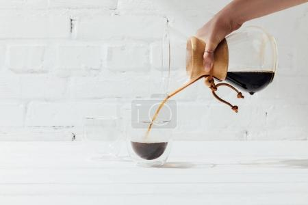 Cropped shot of woman pouring alternative coffee from chemex into glass mug
