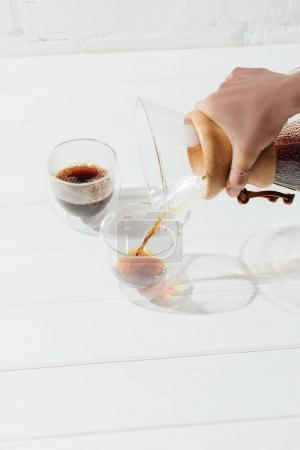 Cropped image of woman pouring alternative coffee from chemex into glass cup
