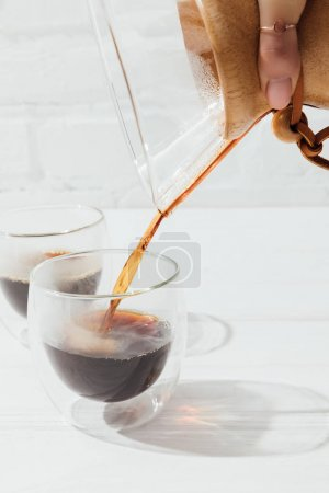 Cropped image of woman pouring alternative coffee from chemex into glass mug
