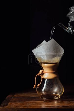 Photo for Hot water pouring into chemex with filter cone on wooden table - Royalty Free Image