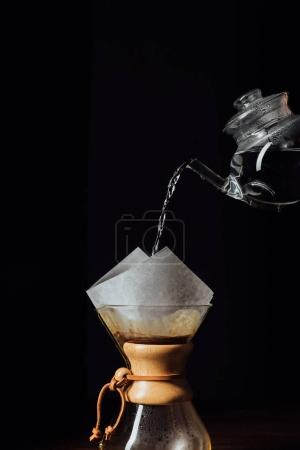 Photo for Hot water pouring into chemex with filter cone, isolated on black - Royalty Free Image