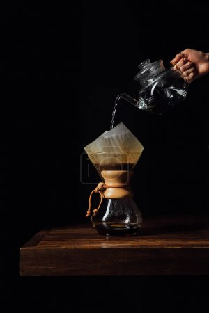 Photo for Cropped image of woman pouring hot water in chemex with filter cone - Royalty Free Image