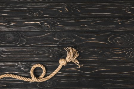 Photo for Top view of knotted brown nautical rope on dark wooden surface - Royalty Free Image