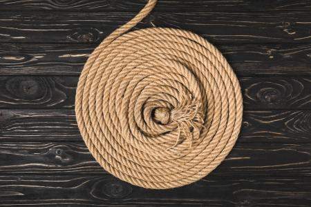 top view of brown knotted nautical rope arranged in circle on wooden surface