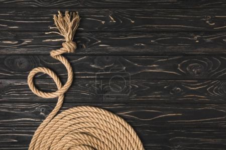 partial view of brown knotted nautical rope arranged in circle on wooden surface