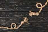 top view of knotted brown nautical ropes on wooden planks
