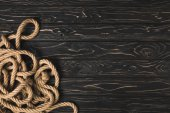 top view of brown nautical rope on dark wooden planks