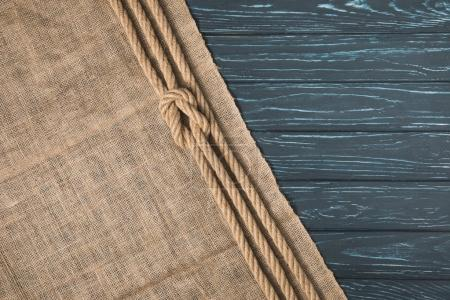 top view of knotted brown nautical rope on sackcloth on wooden background